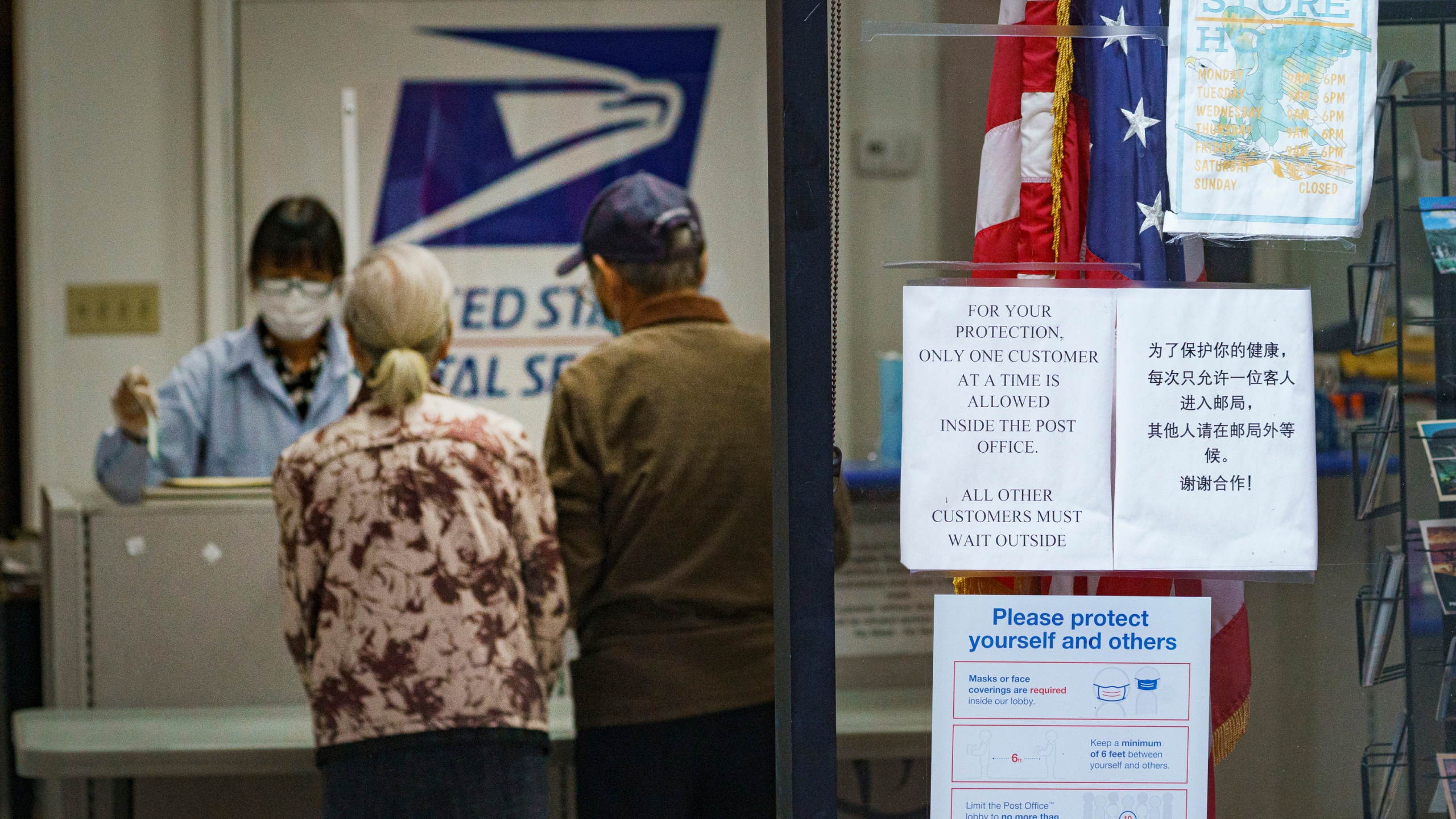 A sign posted at a U.S. post office advises that only one customer at a time is allowed inside, as a senior couple mails a parcel in the Chinatown district of Los Angeles Wednesday, Nov. 18, 2020, during the coronavirus pandemic. (AP Photo/Damian Dovarganes)