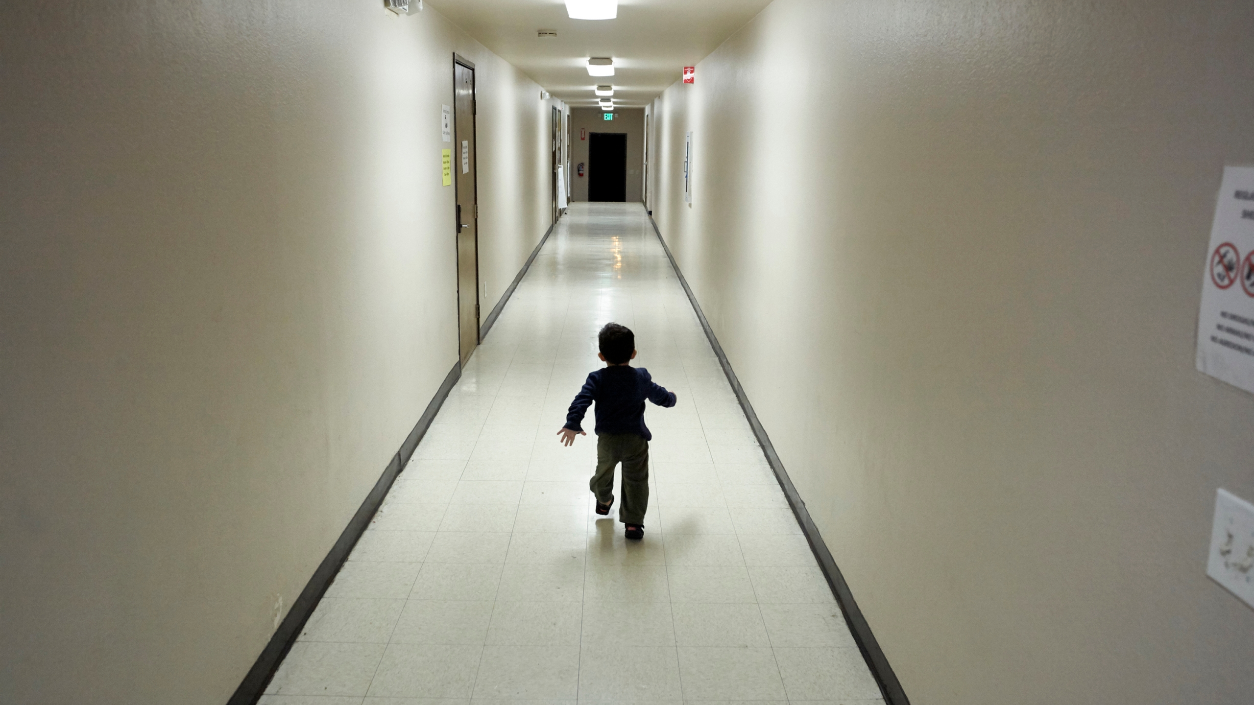 In this Dec. 11, 2018, file photo, an asylum-seeking boy from Central America runs down a hallway after arriving from an immigration detention center to a shelter in San Diego. A court-appointed committee has yet to find the parents of 628 children separated at the border early in the Trump administration. (AP Photo/Gregory Bull, File)