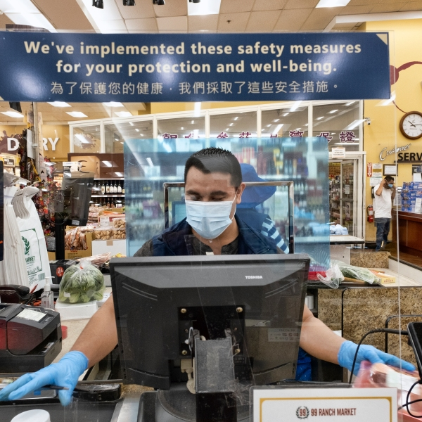 In this May 5, 2020, file photo, a grocery worker, wears a protective mask and gloves, as he helps to check out a customer from behind a plexiglass barrier at a market in Van Nuys. (AP Photo/Richard Vogel, File)