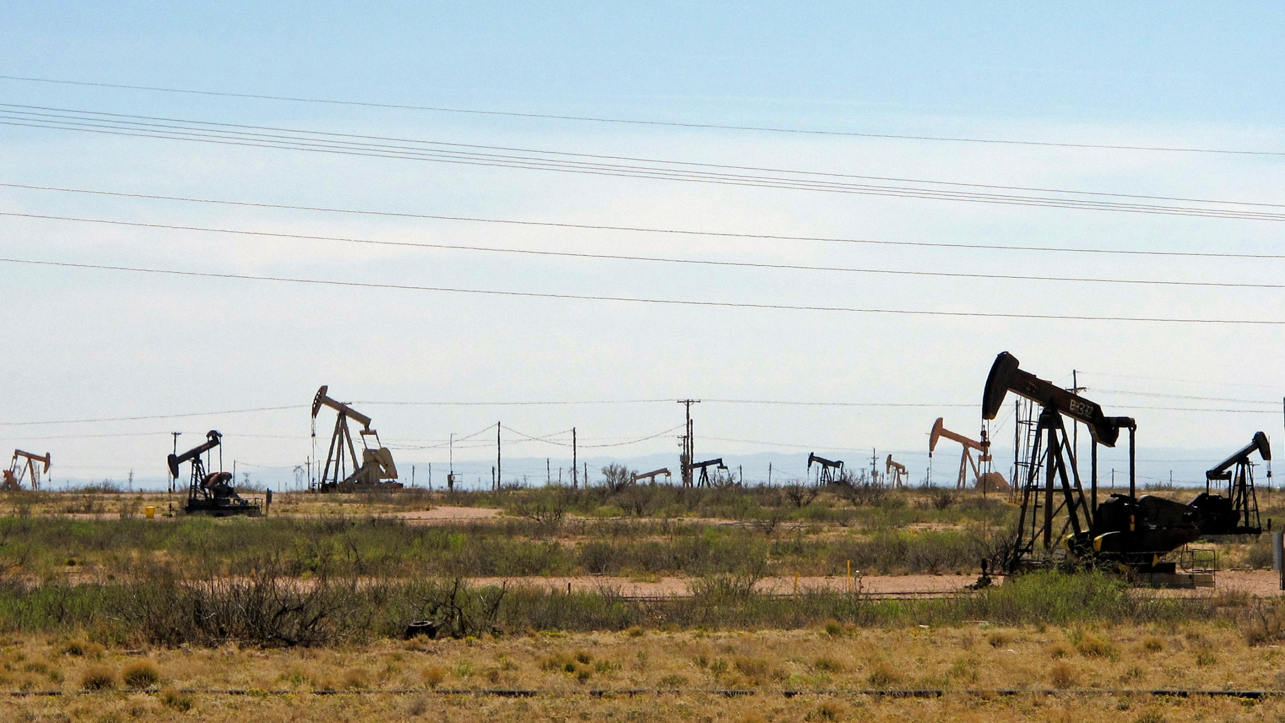 In this April 9, 2014, file photo, oil rigs stand in the Loco Hills field on U.S. Highway 82 in Eddy County near Artesia, N.M., one of the most active regions of the Permian Basin. President Joe Biden is set to announce a wide-ranging moratorium on new oil and gas leasing on U.S. lands, as his administration moves quickly to reverse Trump administration policies on energy and the environment and address climate change. (AP Photo/Jeri Clausing, File)