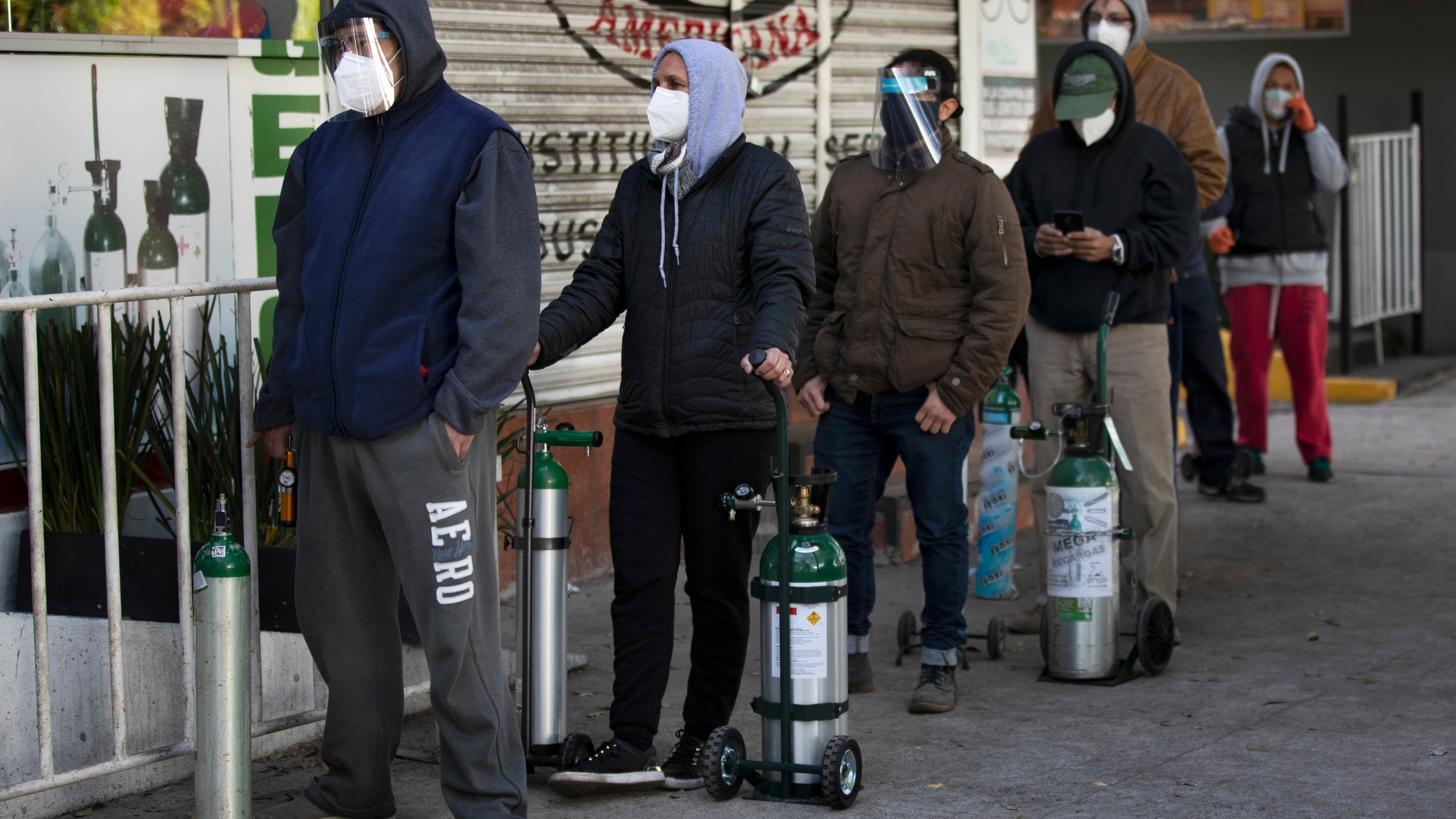 People line up with empty oxygen tanks to refill for family members sick with COVID-19 outside an oxygen store where dozens wait their turn in Mexico City, Thursday, Dec. 31, 2020. (Marco Ugarte/AP Photo)