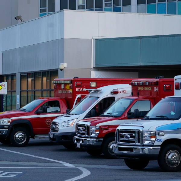 Ambulances are parked outside an emergency room entrance at Long Beach Medical Center Tuesday, Jan. 5, 2021, in Long Beach, Calif. (AP Photo/Ashley Landis)