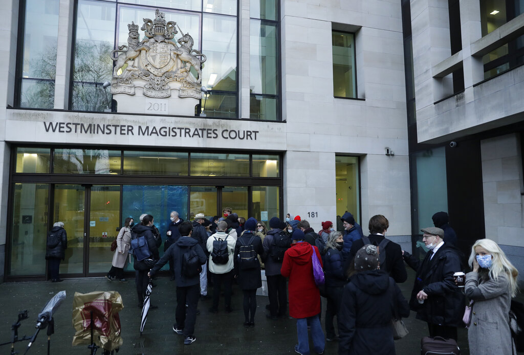 Julian Assange supporters and members of the media queue up outside Westminster Magistrates Court to get a seat at his Bail hearing in London, Wednesday, Jan. 6, 2021. (AP Photo/Matt Dunham)
