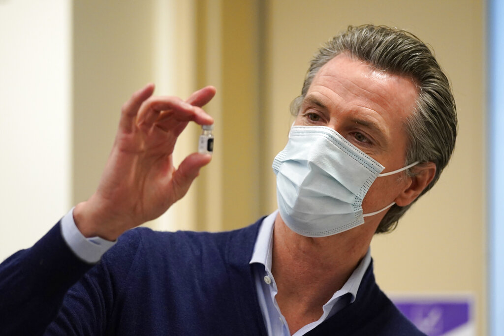 In this Dec. 14, 2020, file photo, California Gov. Gavin Newsom holds up a vial of the Pfizer-BioNTech COVID-19 vaccine at Kaiser Permanente Los Angeles Medical Center in Los Angeles. (AP Photo/Jae C. Hong, File)