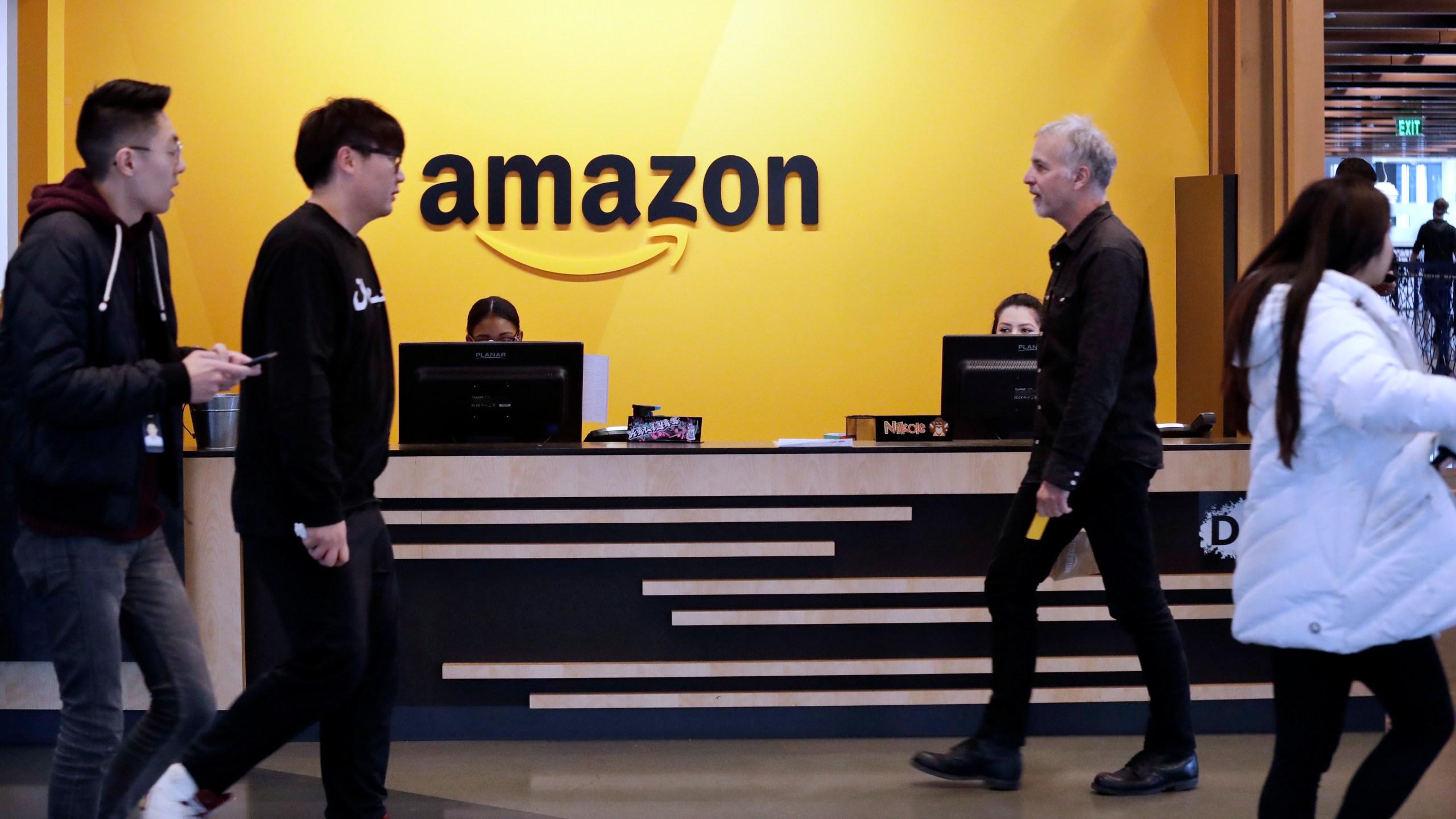 In this Nov. 13, 2018, file photo, employees walk through a lobby at Amazon's headquarters in Seattle. (Elaine Thompson/AP Photo)
