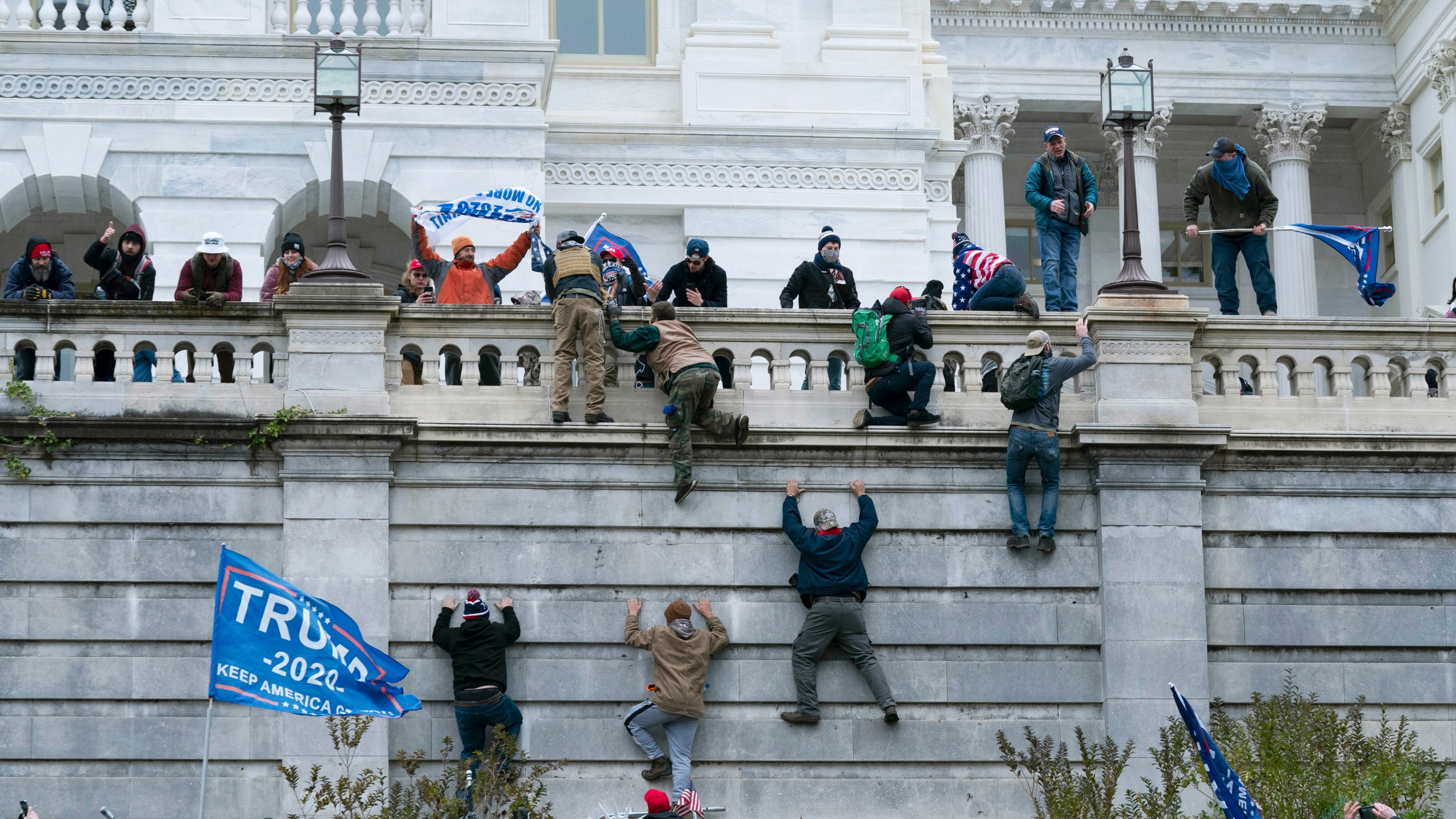 Supporters of Donald Trump climb the west wall of the the U.S. Capitol on Wednesday, Jan. 6, 2021, in Washington. (AP Photo/Jose Luis Magana)