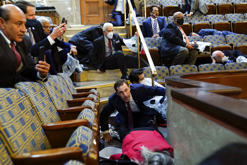People shelter in the House gallery as protesters try to break into the House Chamber at the U.S. Capitol on Jan. 6, 2021, in Washington. (AP Photo/Andrew Harnik)