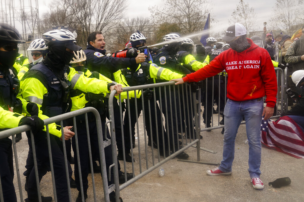 Demonstators loyal to President Donald Trump, are sprayed by police, Wednesday, Jan. 6, 2021, during a day of rioting at the Capitol. (AP Photo/John Minchillo)