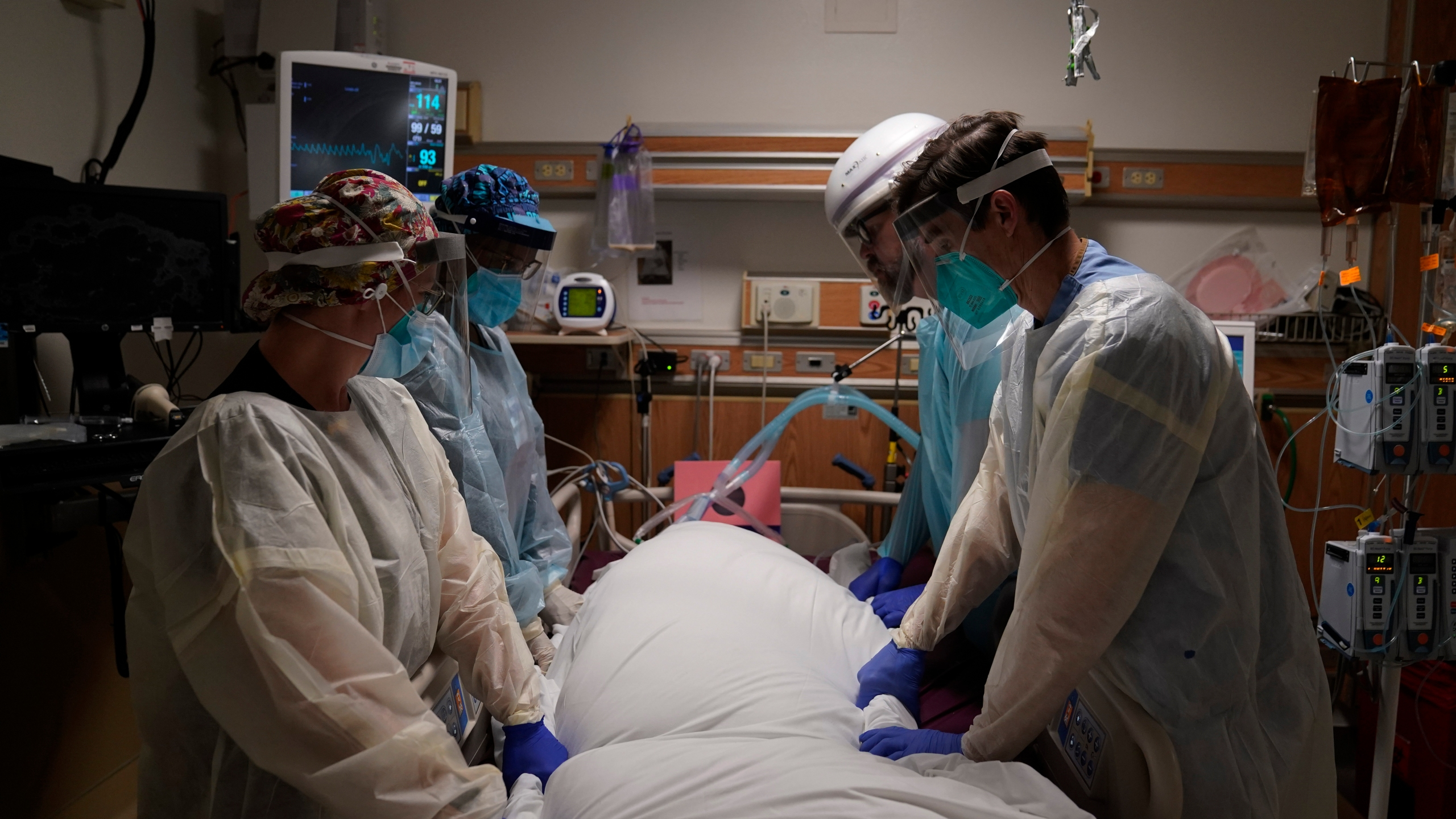 In this Dec. 22, 2020, file photo, medical workers prepare to manually prone a COVID-19 patient in an intensive care unit at Providence Holy Cross Medical Center in the Mission Hills section of Los Angeles. (AP Photo/Jae C. Hong)