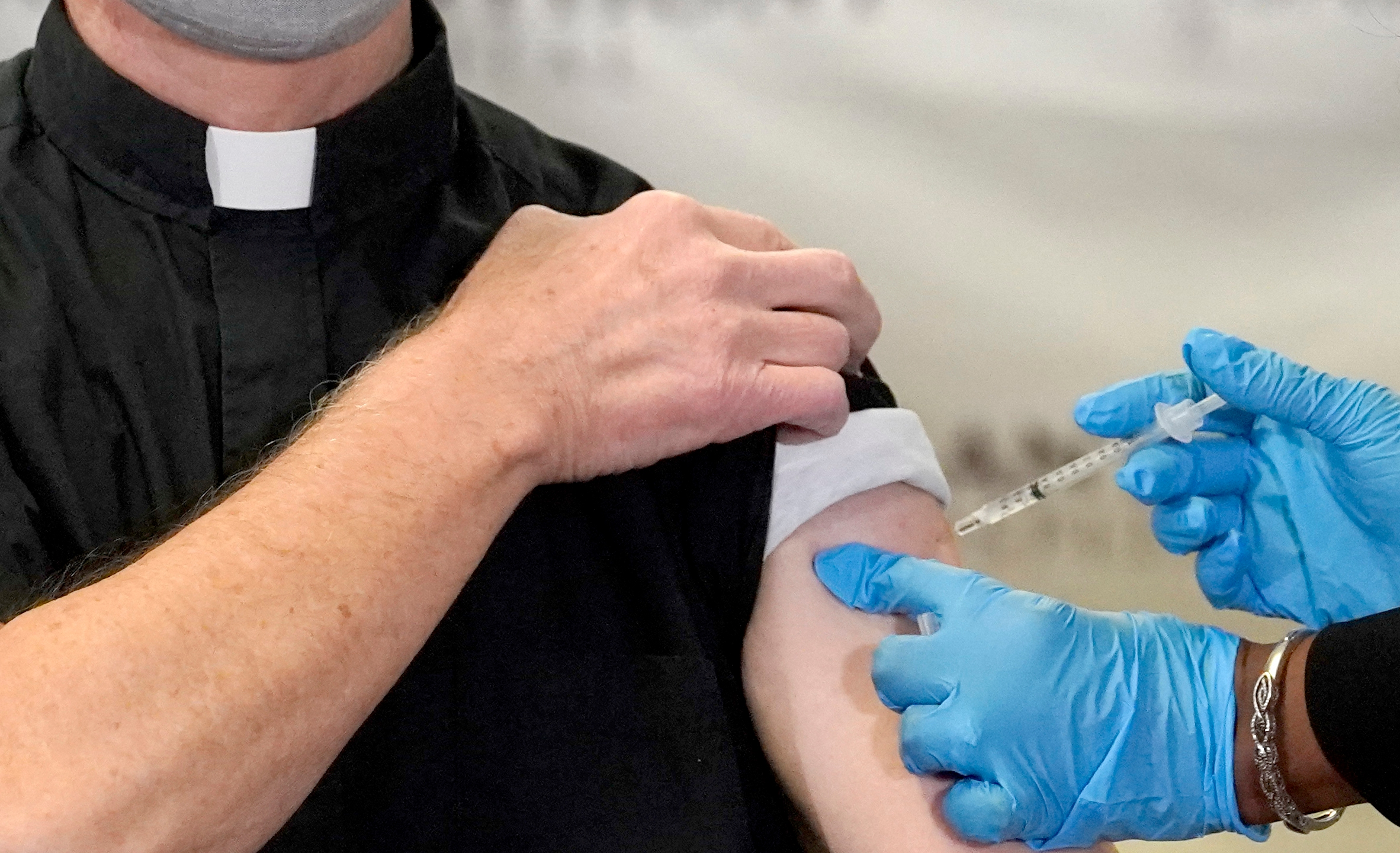 In this Wednesday, Dec. 23, 2020 file photo, a Catholic pastor receives the first of the two Pfizer-BioNTech COVID-19 vaccinations at a hospital in Chicago. (AP Photo/Charles Rex Arbogast)