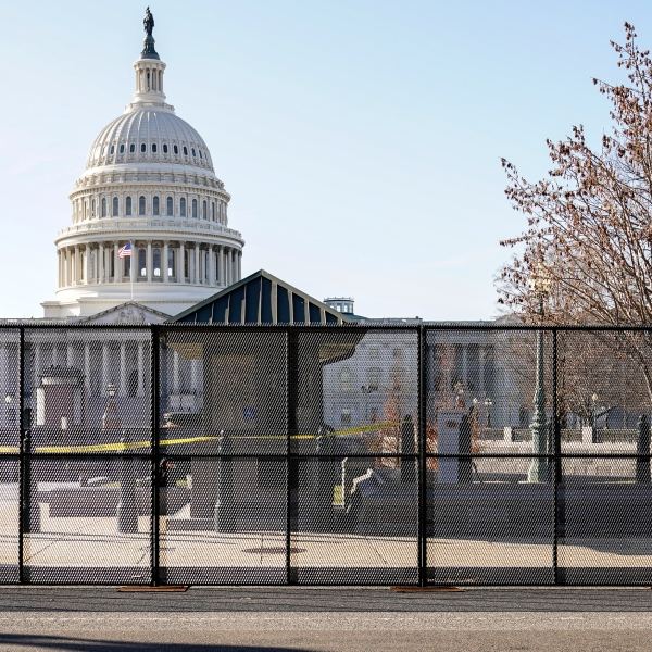 Capitol police officers stand outside of fencing that was installed around the exterior of the Capitol grounds on Jan. 7, 2021, in Washington. (AP Photo/John Minchillo)