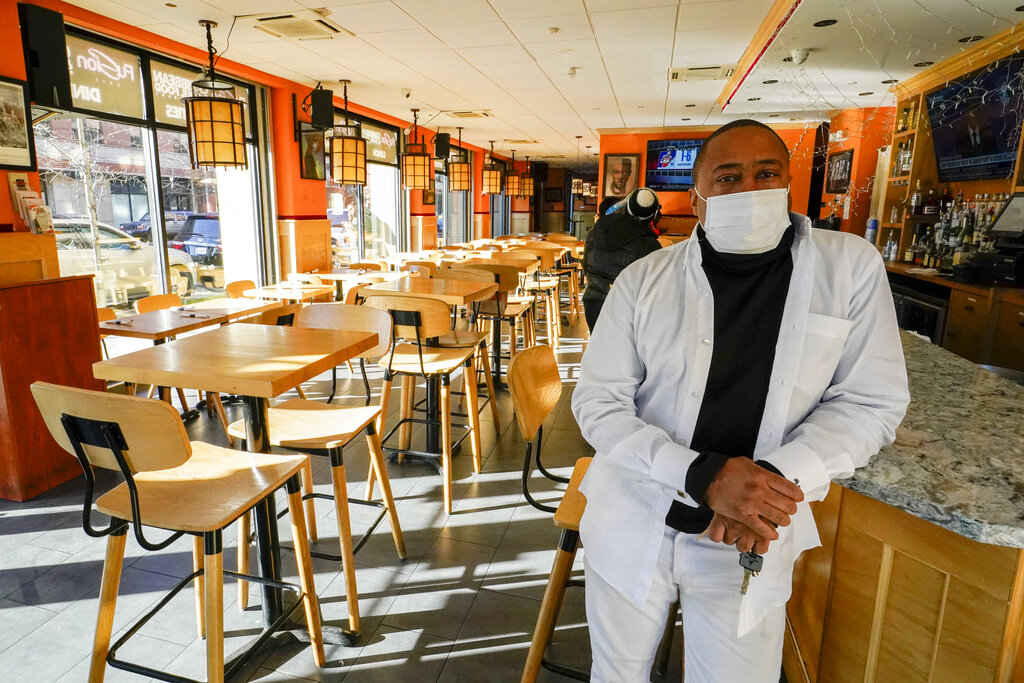 Andrew Walcott, owners of Fusion East Caribbean & Soul Food restaurant, poses for a photo at the restaurant in East New York neighborhood of the Brooklyn borough of New York, Thursday, Jan. 7, 2021. (AP Photo/Mary Altaffer)