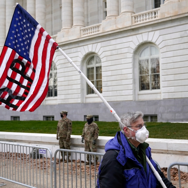 A ma holding a flag walks past the Russell Senate Office Building on Capitol Hill in Washington, Friday, Jan. 8, 2021. (AP Photo/Patrick Semansky)