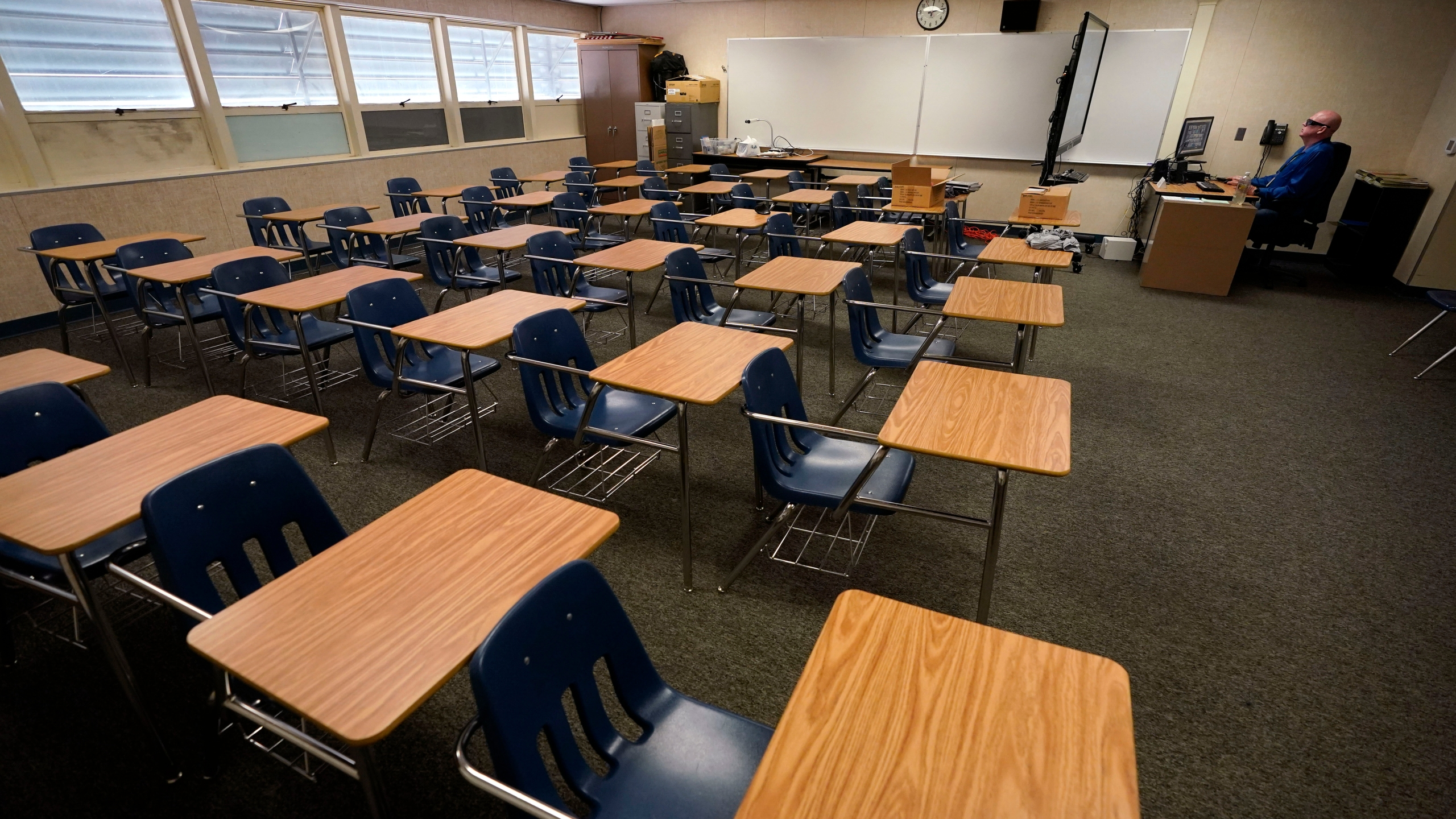 Math teacher Doug Walters sits among empty desks as he takes part in a video conference with other teachers to prepare for at-home learning at Twentynine Palms Junior High School in Twentynine Palms on Aug. 18, 2020. (Gregory Bull / Associated Press)