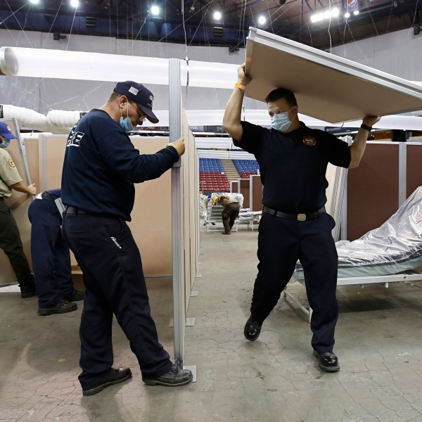 In this April 18, 2020 file photo partitions are installed between beds as work is performed to turn Sleep Train Arena into a 400-bed emergency field hospital to help deal with the coronavirus, in Sacramento. The state has reopened the arena and other facilities to help handle a new surge of coronavirus patients, but is using little more than a handful of volunteers from Gov. Gavin Newsom's California Health Corps who originally helped staff the facility. (AP Photo/Rich Pedroncelli, File)