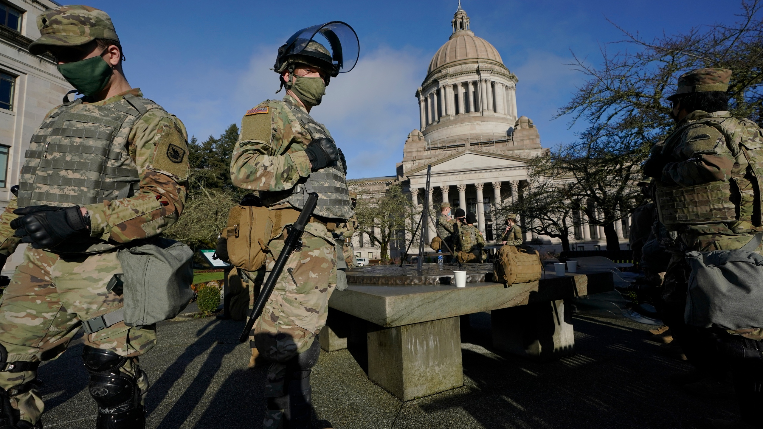 Members of the Washington National Guard stand at a sundial near the Legislative Building, Sunday, Jan. 10, 2021, at the Capitol in Olympia, Wash. (AP Photo/Ted S. Warren)