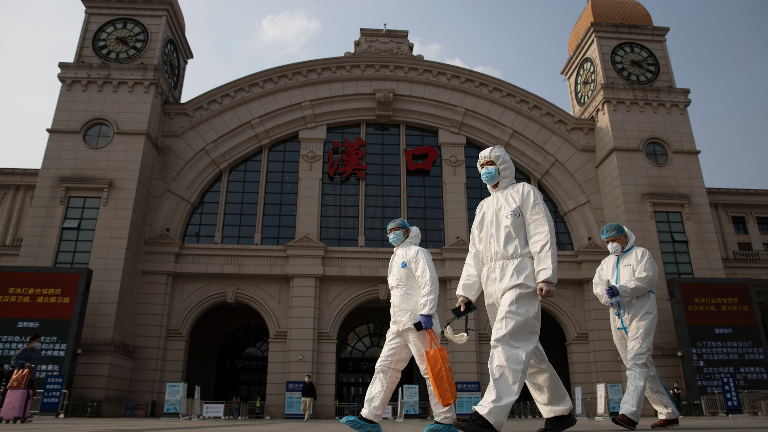 In this April 7, 2020, file photo, workers in protective suits walk past the Hankou railway station on the eve of its resuming outbound traffic in Wuhan in central China's Hubei province. (AP Photo/Ng Han Guan)