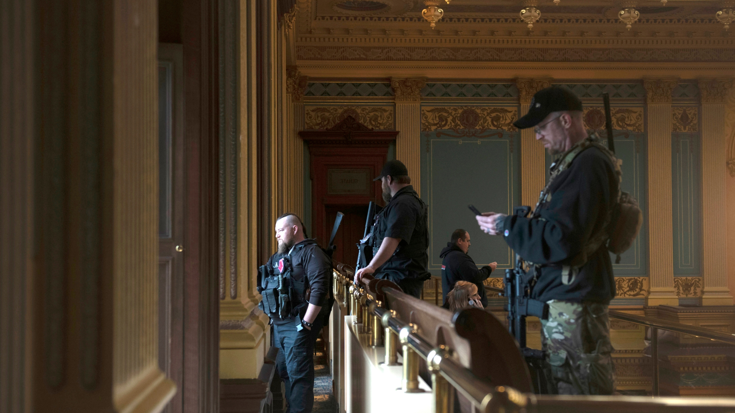 In this April 30, 2020, file photo, armed members of a militia group watch the protest outside while waiting for the Michigan Senate to vote at the Capitol in Lansing, Mich. Michigan has banned the open carry of guns in the state Capitol a week after an armed mob rioted in the U.S. Capitol and following an attempt to storm the statehouse last year. (Nicole Hester/MLive.com/Ann Arbor News via AP File)