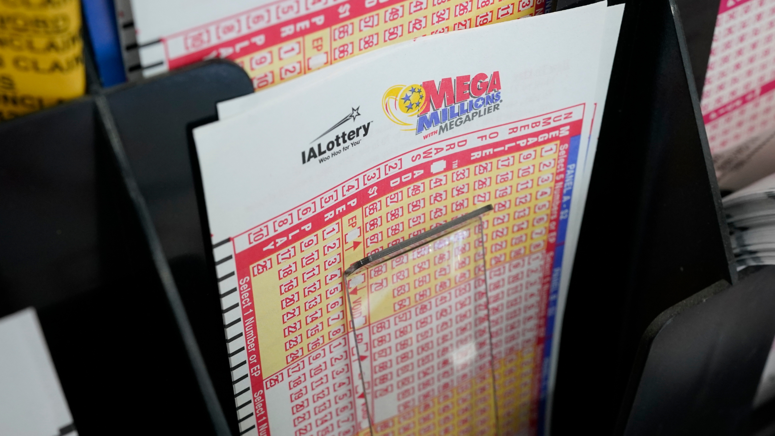 Blank forms for the Mega Millions lottery sit in a bin at a local grocery store, Tuesday, Jan. 12, 2021, in Des Moines, Iowa. (AP Photo/Charlie Neibergall)
