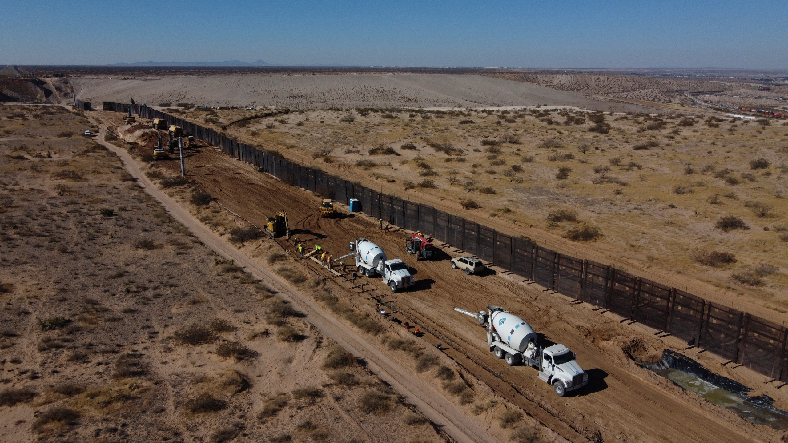 Workers prepare the foundation for a steel section of border wall that will be built on the Mexican side of older metal fencing dividing Ciudad Juarez, Mexico from Sunland Park, New Mexico, on Jan. 12, 2021. (Christian Chavez / Associated Press)