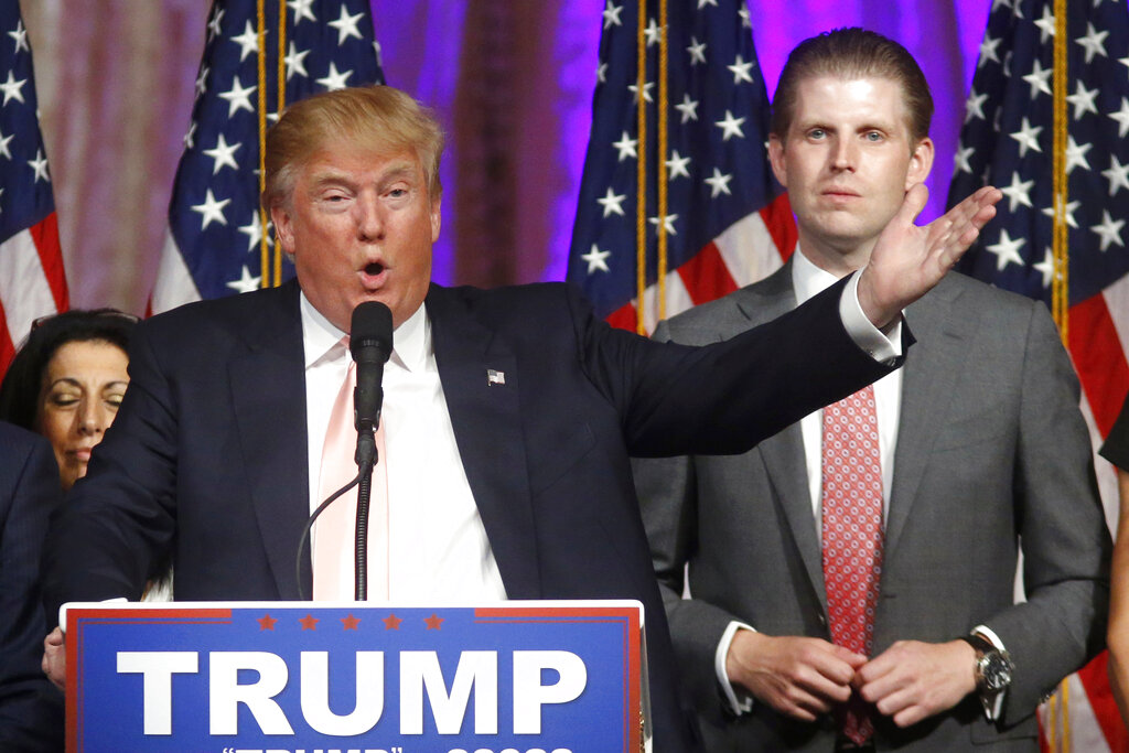 In this Tuesday, March 15, 2016, file photo, Republican presidential candidate Donald Trump speaks to supporters at his primary election night event at his Mar-a-Lago Club in Palm Beach, Fla. At right is his son Eric Trump. (AP Photo/Gerald Herbert, File)