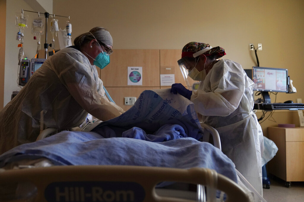 In this Dec. 22, 2020, file photo, registered nurses Robin Gooding, left, and Johanna Ortiz treat a COVID-19 patient at Providence Holy Cross Medical Center in the Mission Hills section of Los Angeles. (AP Photo/Jae C. Hong, File)