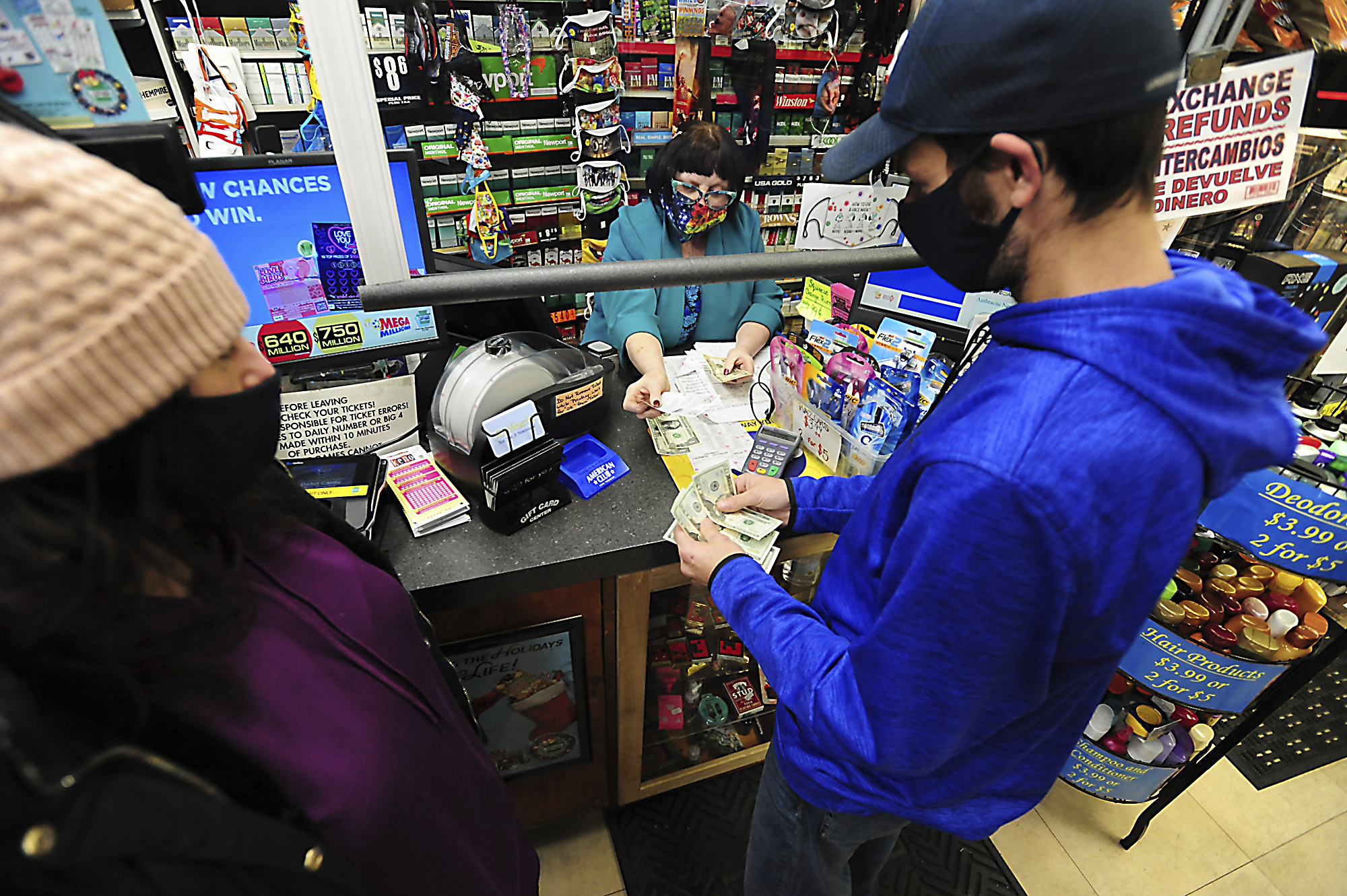 Michael and Amanda Lazovich of Plain, Pa., purchase Powerball and Mega Millions lottery tickets at the Anthracite Newsstand on Public Square in Wilkes-Barre, Pa., Thursday, Jan. 14, 2021. (Mark Moran/The Citizens' Voice via AP)