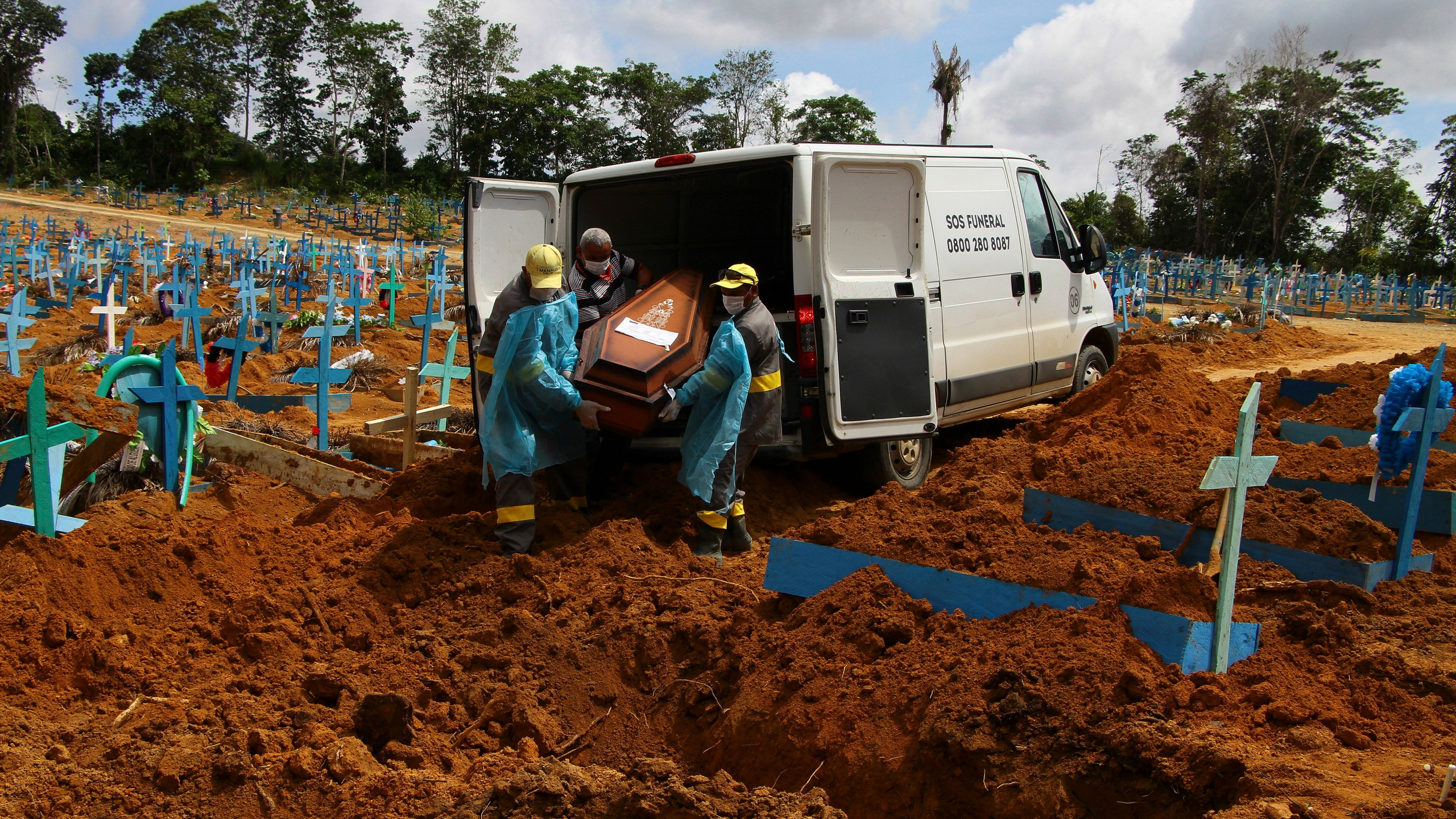 In this Jan. 6, 2021, file photo, cemetery workers carry the remains of 89-year-old Abilio Ribeiro, who died of the coronavirus, to bury at the Nossa Senhora Aparecida cemetery in Manaus, Amazonas state, Brazil. (AP Photo/Edmar Barros)