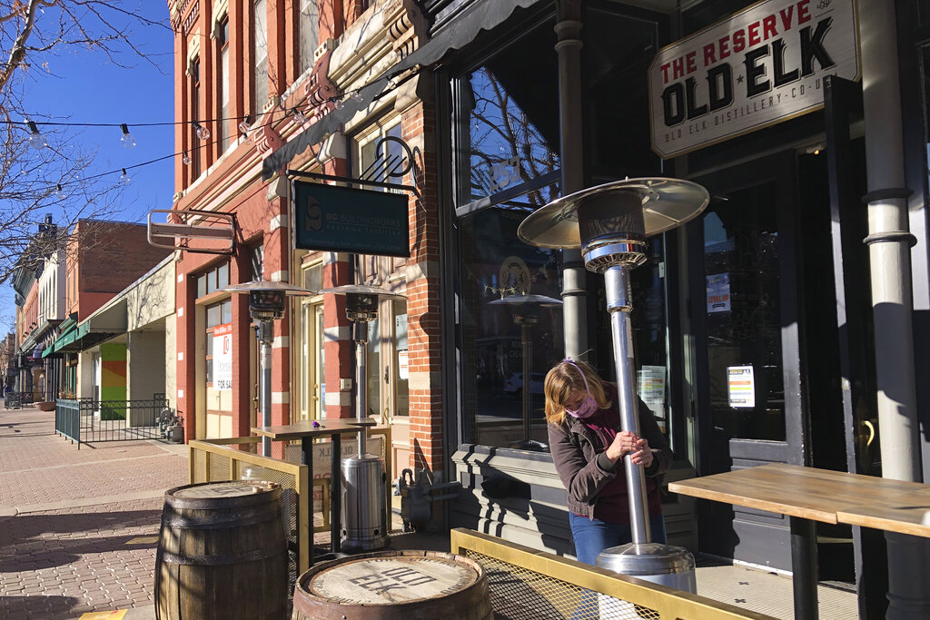 Whiskey tasting room manager Melinda Maddox moves a propane-fueled outdoor space heater in downtown Fort Collins, Colo., in preparation for opening on Jan. 6, 2021. (AP Photo/Mead Gruver)