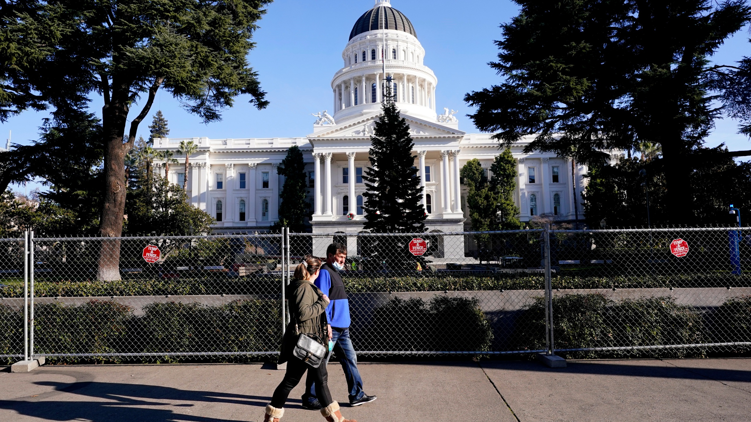 A temporary six-foot high chain link fence surrounds the state Capitol because of concerns over the potential for civil unrest, in Sacramento, Calif., Thursday, Jan. 14, 2021. (AP Photo/Rich Pedroncelli)