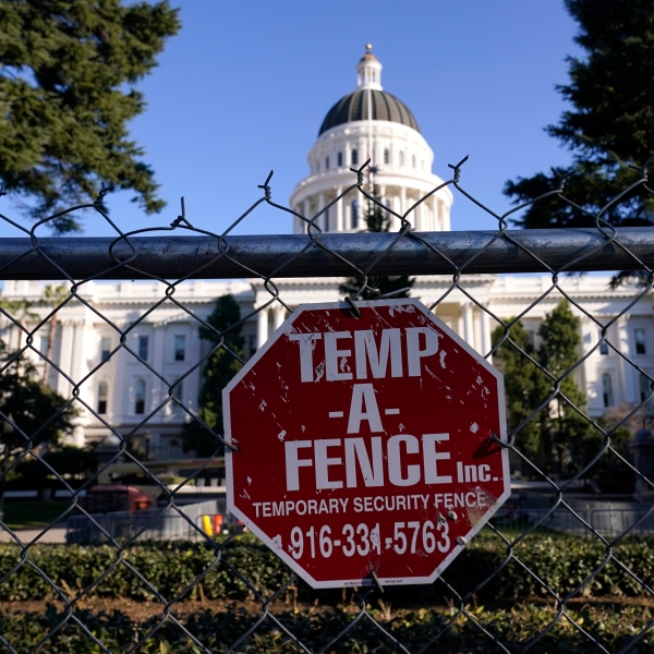 A temporary six-foot high chain link fence surrounds the state Capitol because of concerns over the potential for civil unrest, in Sacramento on Jan. 14, 2021. (AP Photo/Rich Pedroncelli)