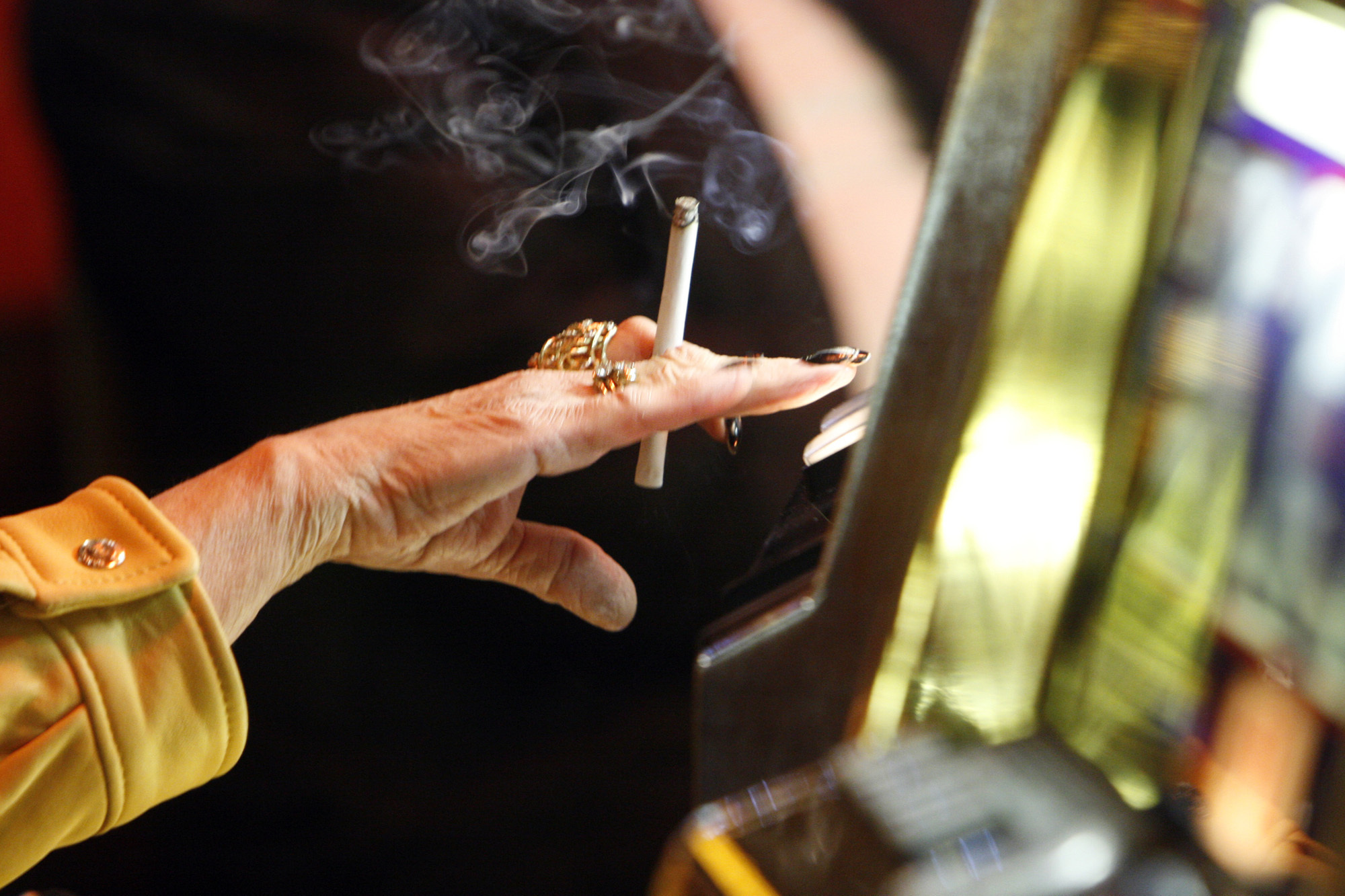 A woman holds a cigarette in her hand as she plays a slot machine at the Trump Taj Mahal in Atlantic City, N.J., on April 8, 2008. (Cie Stroud / Associated Press)