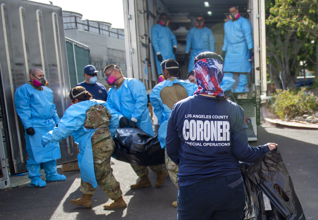 "In this Jan. 12, 2020 file photo, provided by the LA County Dept. of Medical Examiner-Coroner Elizabeth ""Liz"" Napoles, right, works alongside with National Guardsmen who are helping to process the COVID-19 deaths to be placed into temporary storage at LA County Medical Examiner-Coroner Office in Los Angeles. (LA County Dept. of Medical Examiner-Coroner via AP, File)"