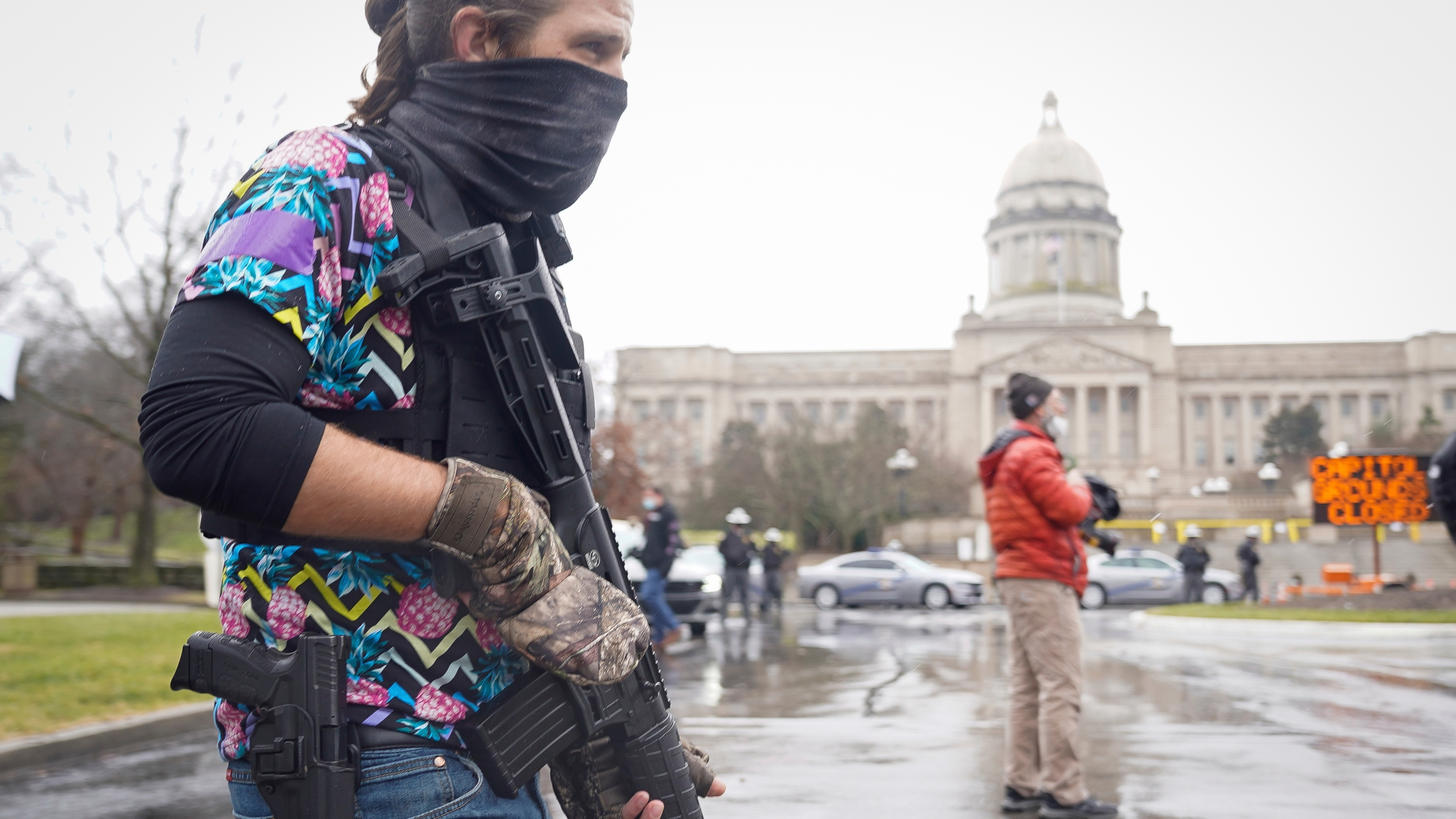 A Black Lives Matter activist carrying a semi-automatic rifle walks outside at the Capitol building in Frankfort, Ky., Wednesday, Jan 17, 2021. (AP Photo/Bryan Woolston)