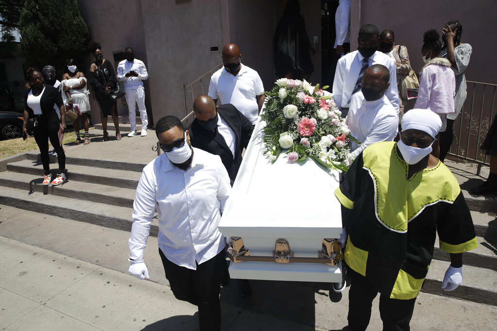 In this July 21, 2020, file photo, pall bearers carry a casket with the body of Lydia Nunez, who died from COVID-19, after a funeral service at the Metropolitan Baptist Church in Los Angeles. (AP Photo/Marcio Jose Sanchez, File)