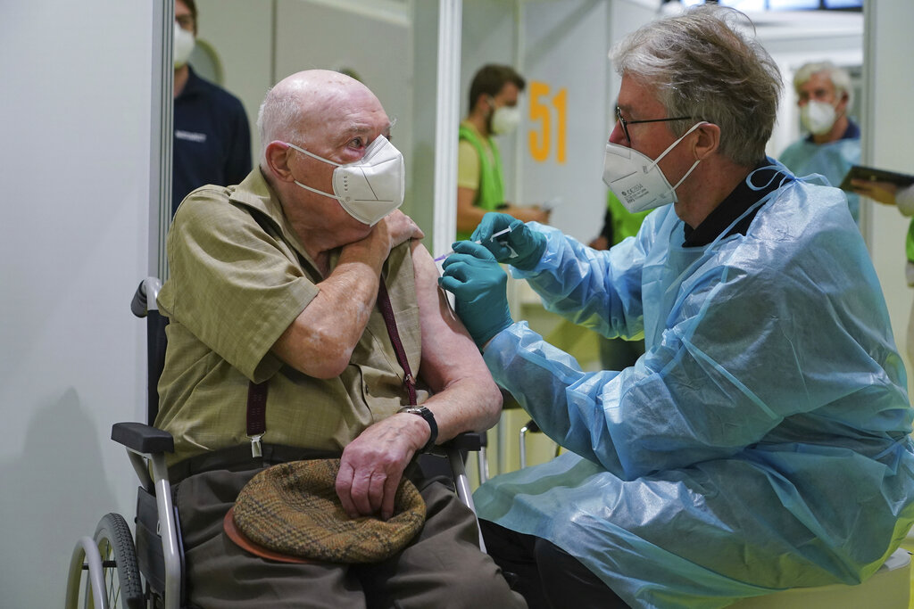 A doctor inoculates Herri Rehfeld, 92, against the new coronavirus with the Pfizer/BioNTech vaccine at the vaccination center at the Messe Berlin trade fair grounds on the center's opening day in Berlin, Germany, Monday, Jan. 18, 2021. (Sean Gallup/Getty Images via AP, Pool)