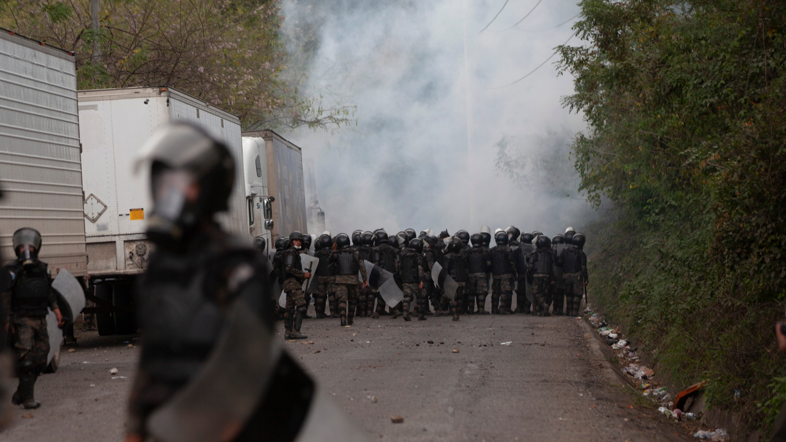 A cloud of tear gas rises as Guatemalan soldiers and police clash with migrants at a roadblock on the highway in Vado Hondo, Guatemala, Monday, Jan. 18, 2021. The roadblock was strategically placed at a chokepoint on the two-lane highway flanked by a tall mountainside and a wall leaving the migrants with few options. (AP Photo/Sandra Sebastian)