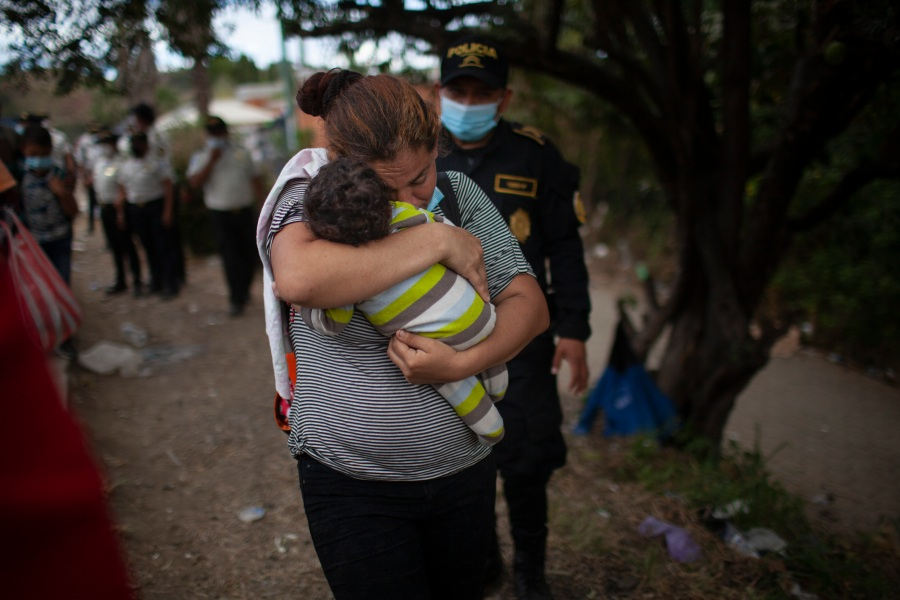 A woman carries her son as Honduran migrants confront Guatemalan soldiers and police manning a roadblock that prevents them from advancing toward the U.S., on the highway in Vado Hondo, Guatemala, on Jan. 18, 2021. (Sandra Sebastian / Associated Press)
