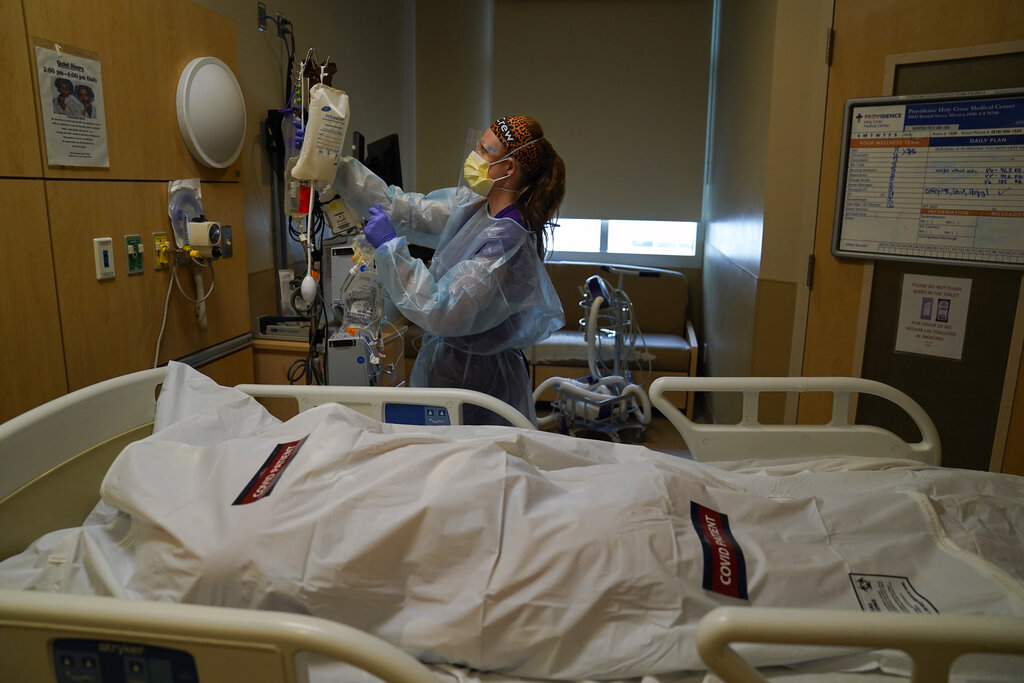 Registered nurse Nikki Hollinger cleans up a room as a body of a COVID-19 victim lies in a body bag at Providence Holy Cross Medical Center in Mission Hills on Jan. 9, 2021. (AP Photo/Jae C. Hong)