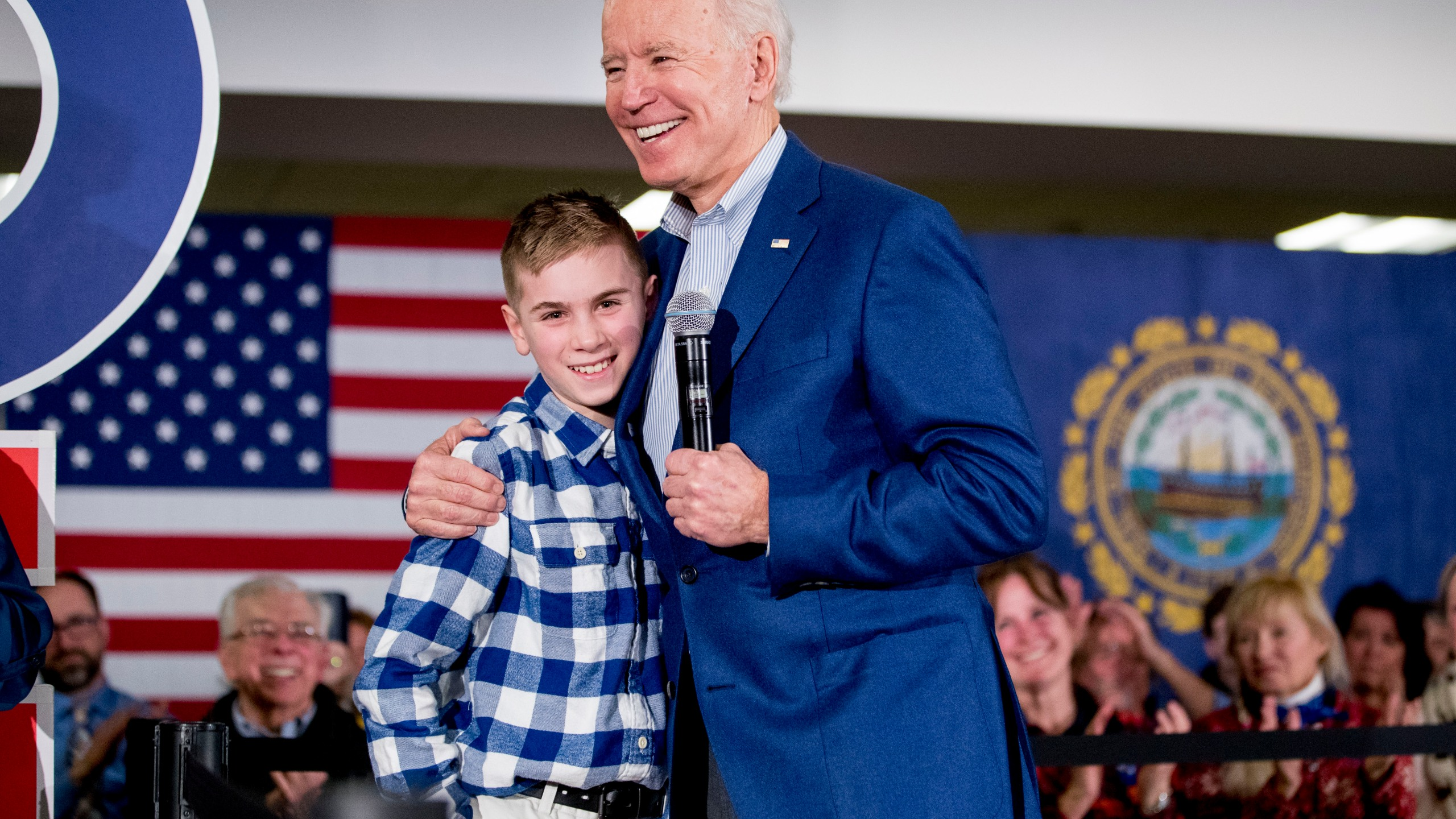 "Then Democratic presidential candidate former Vice President Joe Biden hugs Brayden Harrington at a campaign stop in Gilford, N.H. on Feb. 10, 2020. Harrington, who will be part of a primetime inaugural special, has a book coming out this summer. His picture story ""Brayden Speaks Up"" will be released Aug. 10. (AP Photo/Andrew Harnik, File)"