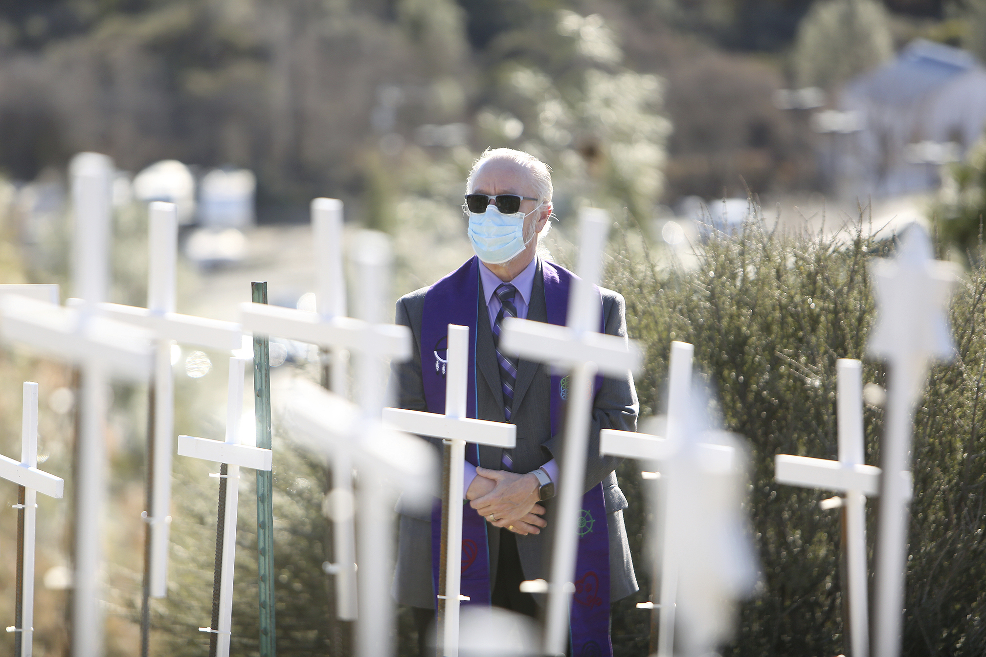 Senior Minister Rev. Rafe Ellis, of Sierra Center for Spiritual Living, gets a close look at the COVID Memorial placed on the Old Barn Self Storage property adjacent to the Golden Center Freeway Tuesday, Jan. 19, 2021 in Grass Valley, Calif. (Elias Funez/The Union via AP)