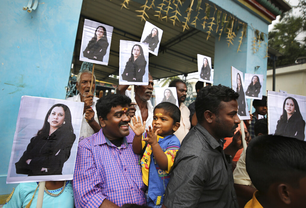 A child reacts as villagers hold placards featuring U.S. Vice President-elect Kamala Harris after participating in special prayers ahead of her inauguration, outside a Hindu temple in Thulasendrapuram, the hometown of Harris' maternal grandfather, south of Chennai, Tamil Nadu state, India on Jan. 20, 2021. (AP Photo/Aijaz Rahi)
