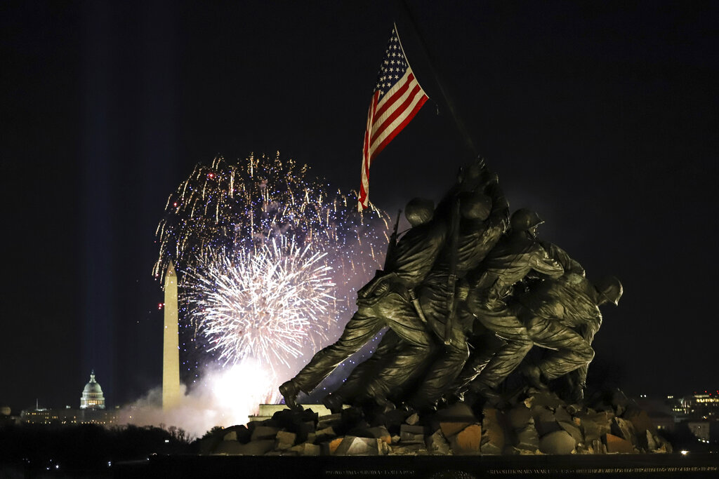 Fireworks explode over the Washington Monument with the Marine Corps War Memorial in the foreground, Wednesday, Jan. 20, 2021, in Arlington, Va., as part of the festivities after President Joe Biden was inaugurated as the 46th president of the United States. (AP Photo/Shafkat Anowar)