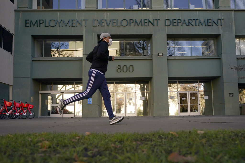 In his Dec. 18, 2020 file photo a runner passes the office of the California Employment Development Department in Sacramento. (AP Photo/Rich Pedroncelli, File)