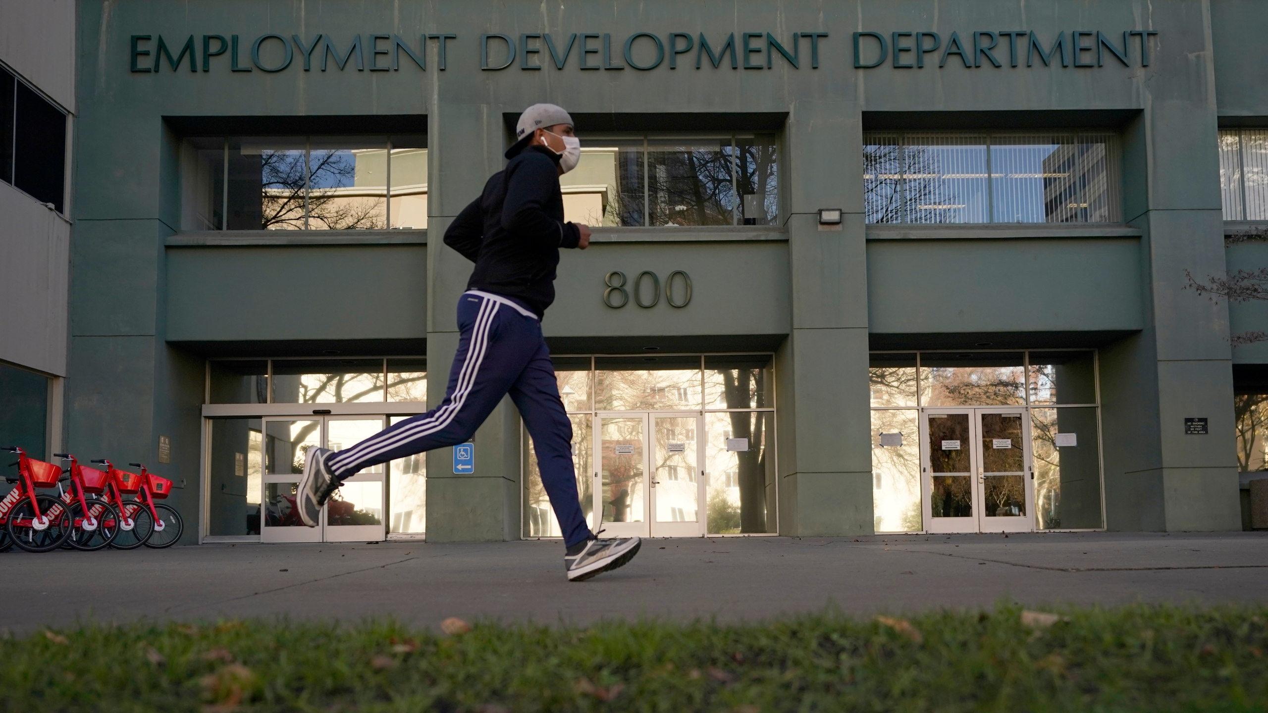 In this Dec. 18, 2020 file photo a runner passes the office of the California Employment Development Department in Sacramento, Calif. (AP Photo/Rich Pedroncelli)