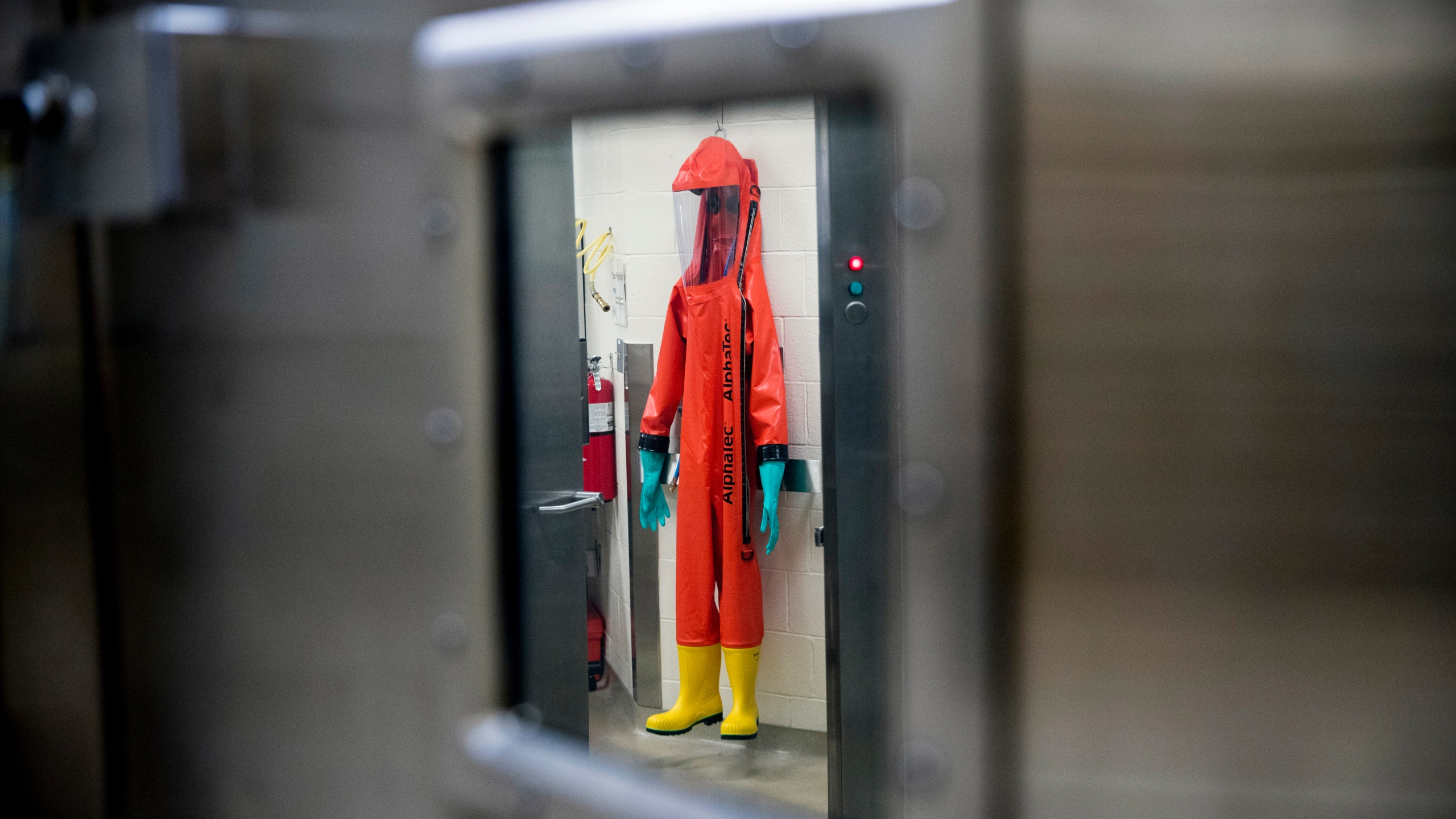 In this March 19, 2020, file photo, a biosafety protective suit for handling viral diseases are hung up in a biosafety level 4 training facility at U.S. Army Medical Research and Development Command at Fort Detrick in Frederick, Md., where scientists are working to help develop solutions to prevent, detect and treat the coronavirus. (AP Photo/Andrew Harnik)