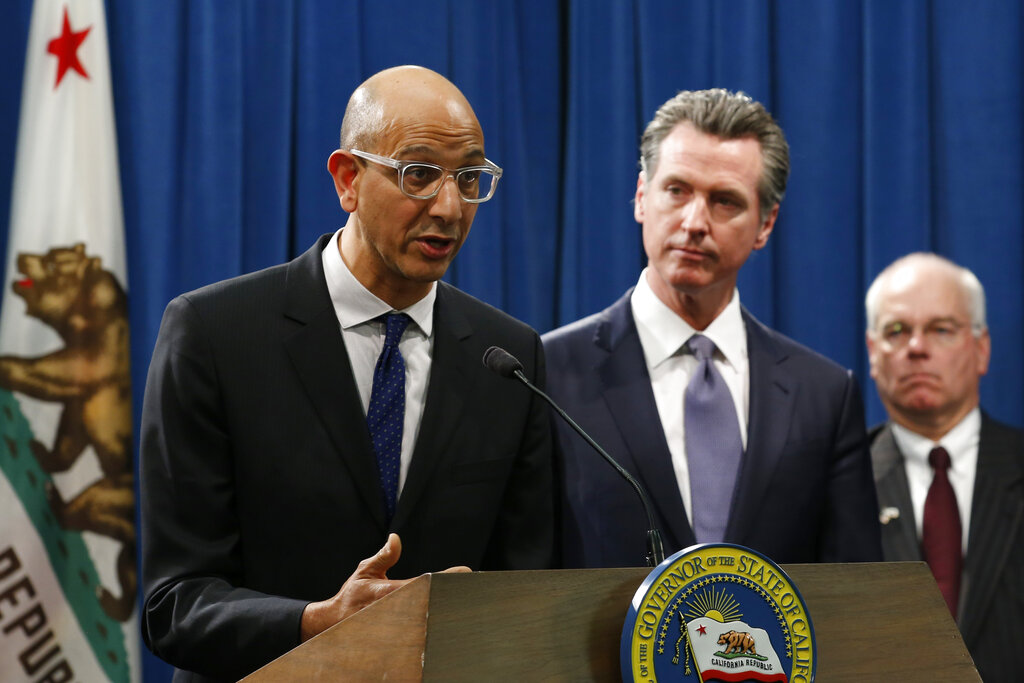 In this March 12, 2020, file photo Dr. Mark Ghaly, secretary of the California Health and Human Services, discusses the coronavirus as Gov. Gavin Newsom, center, listens at a news conference in Sacramento, Calif. (AP Photo/Rich Pedroncelli, File)