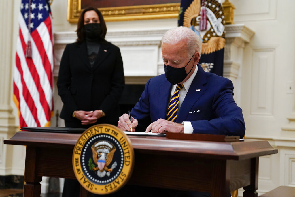 President Joe Biden signs executive orders on the economy in the State Dining Room of the White House, Friday, Jan. 22, 2021, in Washington. (AP Photo/Evan Vucci)