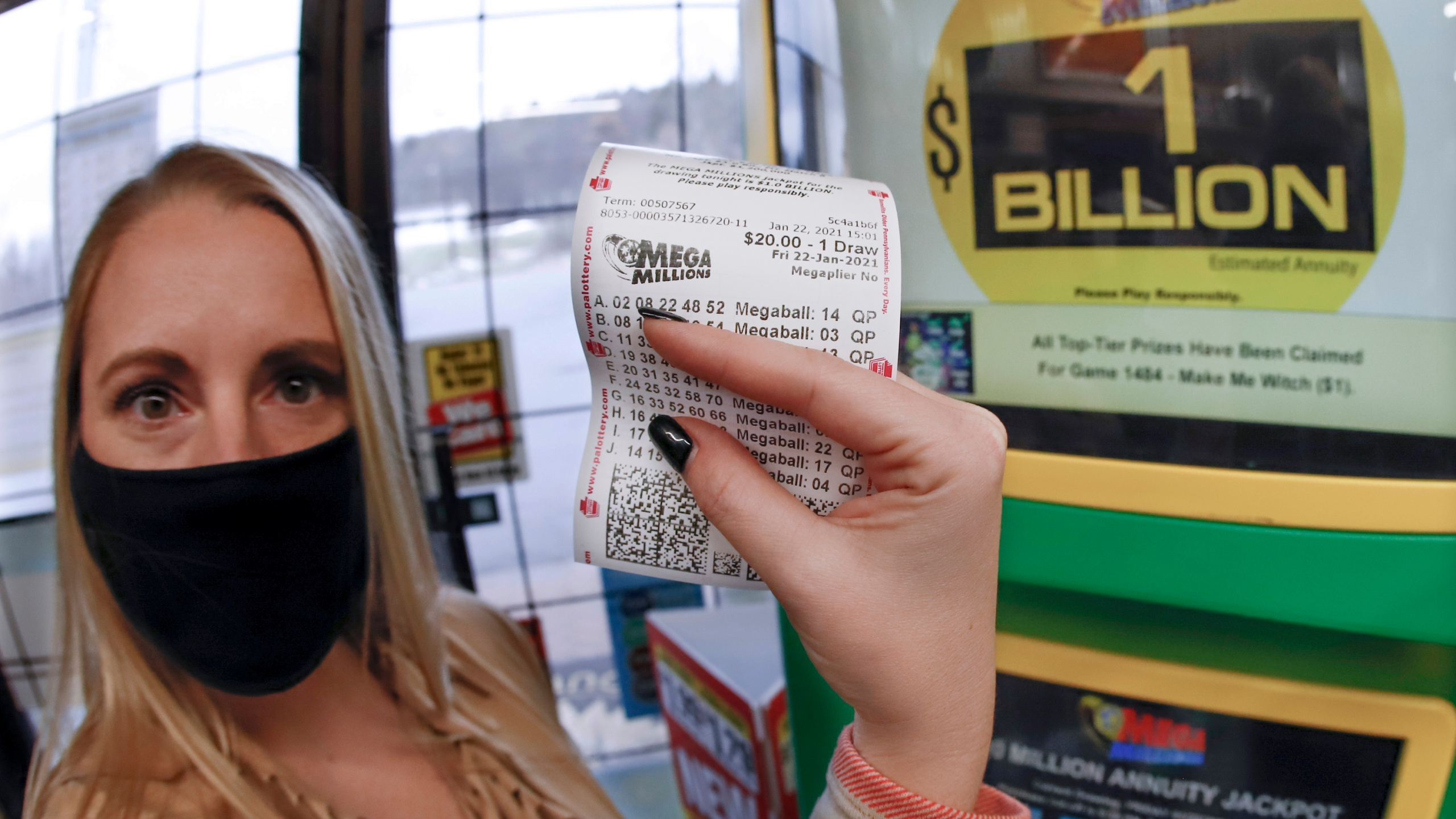 A patron, who did not want to give her name, shows the ticket she had just purchased for the Mega Millions lottery drawing at the lottery ticket vending kiosk in a Smoker Friendly store, Friday, Jan. 22, 2021, in Cranberry Township, Pa. (AP Photo/Keith Srakocic)