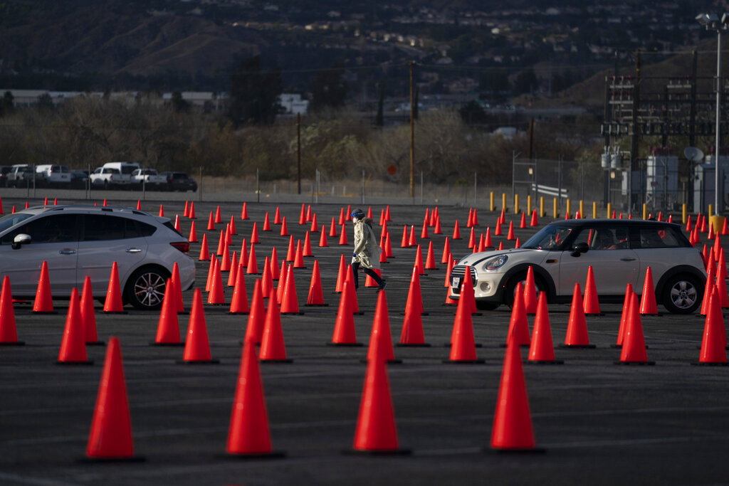 In this Jan. 22, 2021 file photo medical staff members walk between traffic cones at a mass COVID-19 vaccination site set up in the parking lot of Six Flags Magic Mountain in Valencia, Calif. Five weeks into its vaccination program, California still doesn't have nearly the supply to meet demand and there's growing angst among residents over the difficulty to even get in line for a shot. Social media is awash with people seeking or giving tips on how to maneuver through the system. (AP Photo/Jae C. Hong,File)